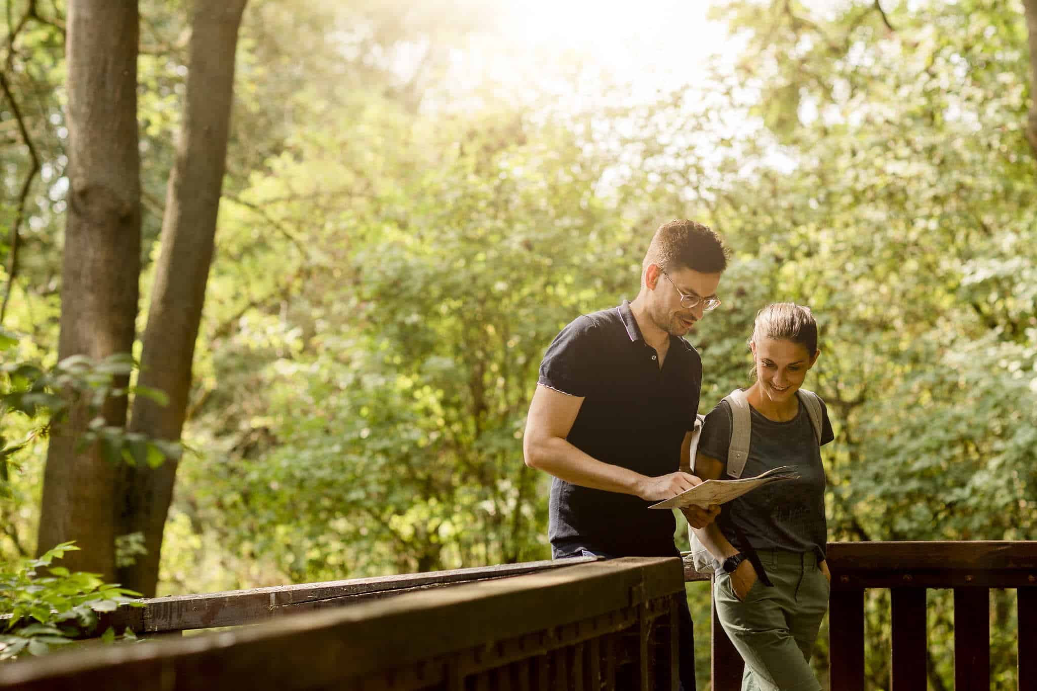 Couple looks at map in the forest