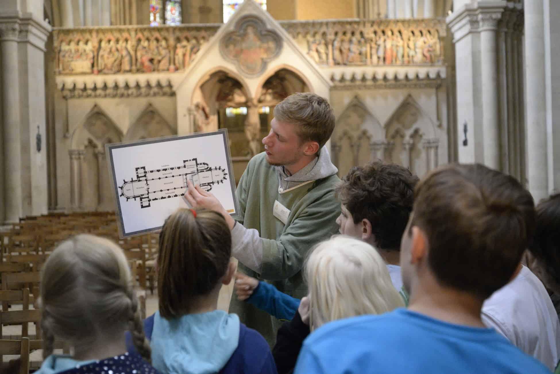 Tourleiter zeigt Kindern Aufbau des Domes